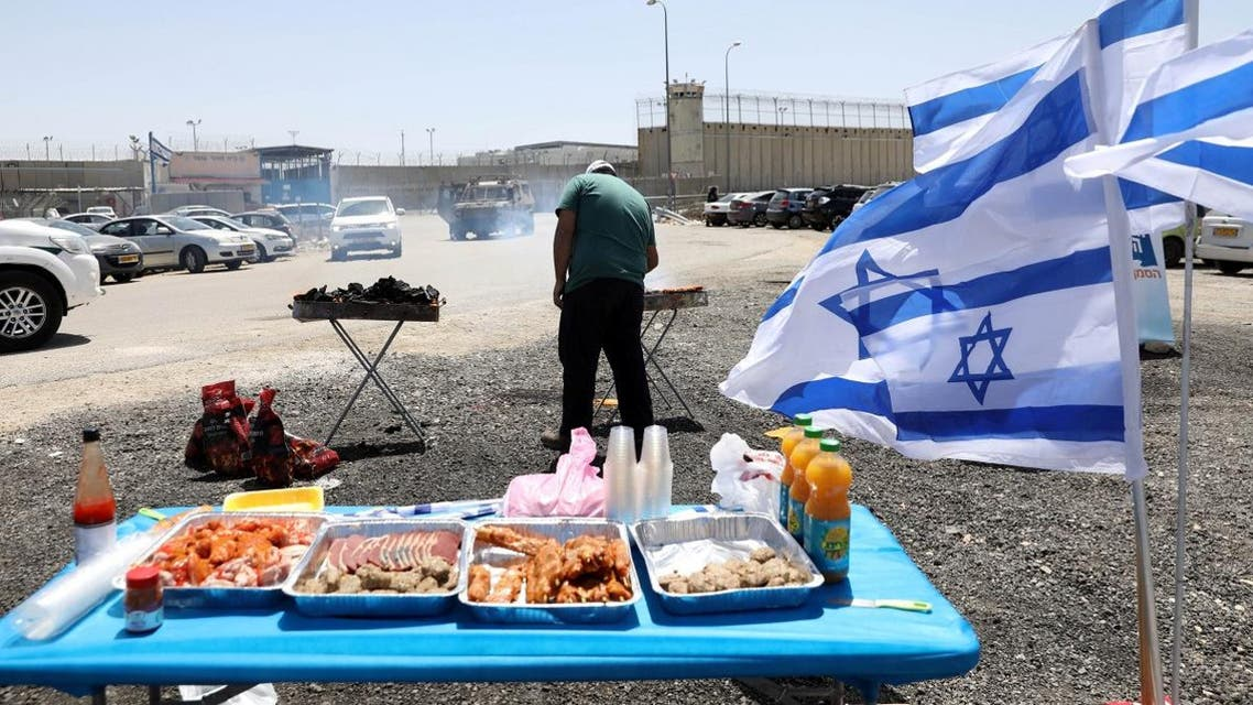sraelis have a BBQ outside Ofer Prison while Palestinians rally in support of Palestinian prisoners on hunger strike in Israeli jails over the fence. (Reuters)