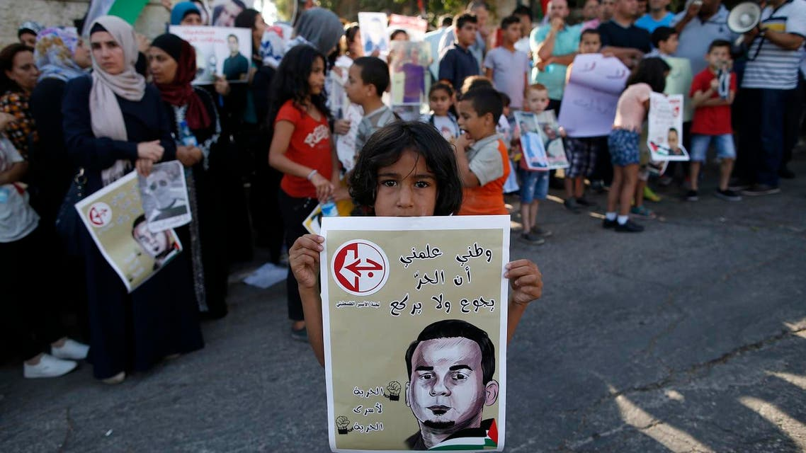 A Palestinian girl holds a poster with a picture of Bilal Kayed, during a demonstration against his detention by the Israeli authorities, near the Red Cross offices in East Jerusalem on August 3, 2016. (AFP)