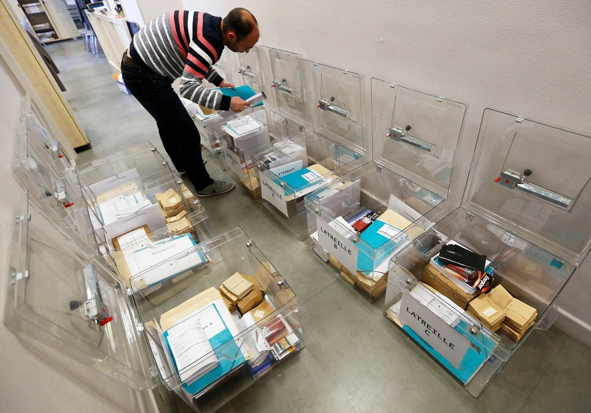 A municipal employee prepares ballot boxes on the eve of the first round of the French presidential election, at a polling station in Tulle, Southwestern France. (Reuters)