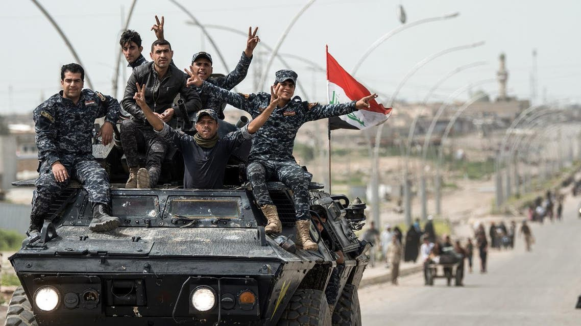 Members of the Iraqi federal police flash the victory gesture as they sit on an armoured personnel carrier (APC) on a road in west Mosul on April 21, 2017. (AFP)