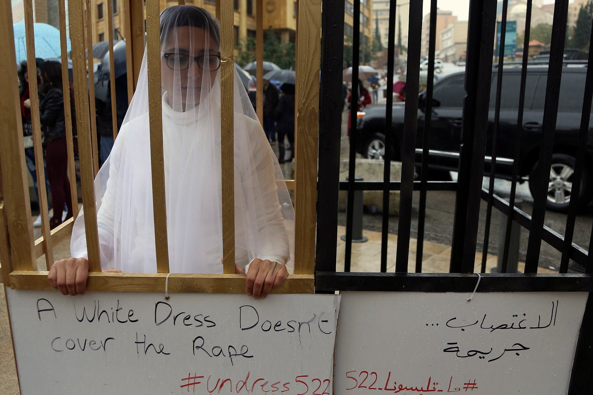 An activist from the Lebanese NGO Abaad, stands in a golden cage dressed as a bride in a white wedding dress while she demonstrates in front of the government building in downtown Beirut, Lebanon, Wednesday, March 15, 2017. (AP)