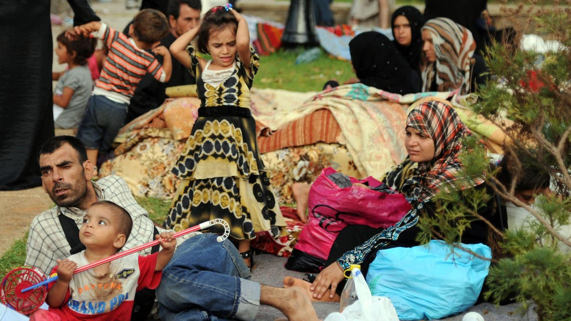 Syrian nationals fleeing the conflict in their home country gather in a garden in Port Said Square in Algiers on July 28, 2012. AFP PHOTO/FAROUK BATICHE