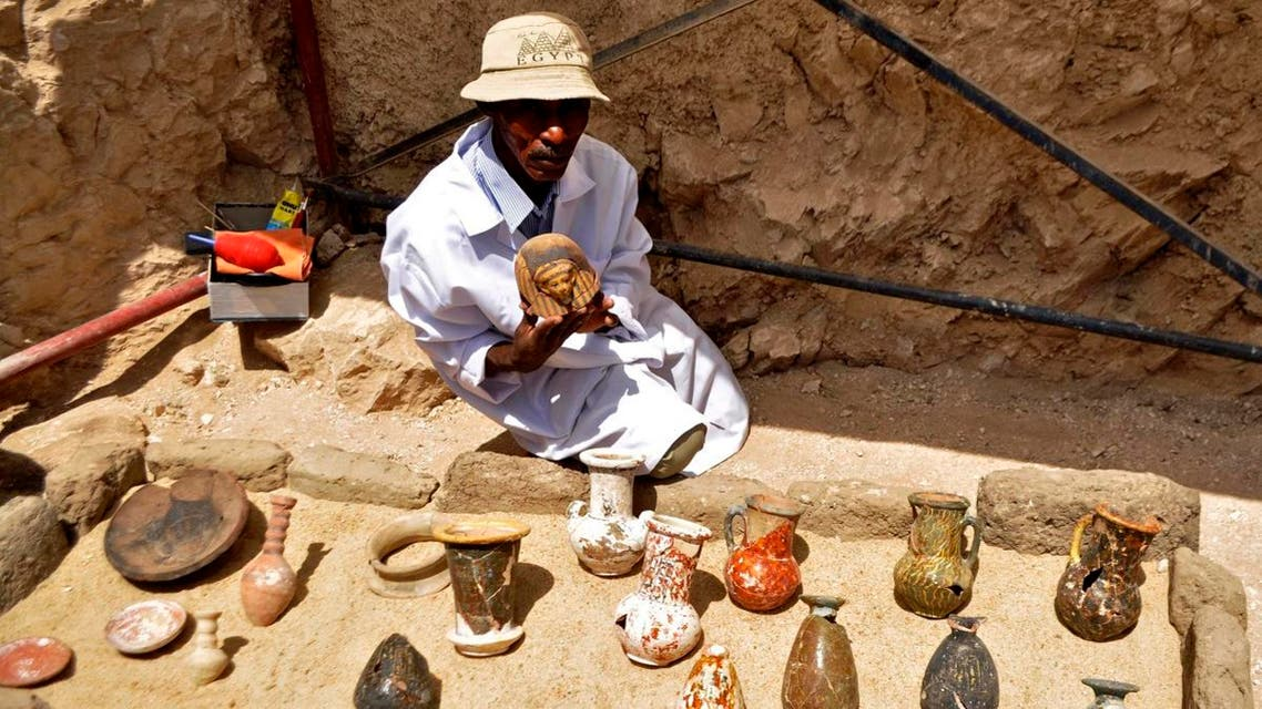 A member of an Egyptian archaeological team shows artifacts discovered in a 3,500-year-old tomb in the Draa Abul Nagaa necropolis, near the southern city of Luxor, on April 18, 2017. (AFP)