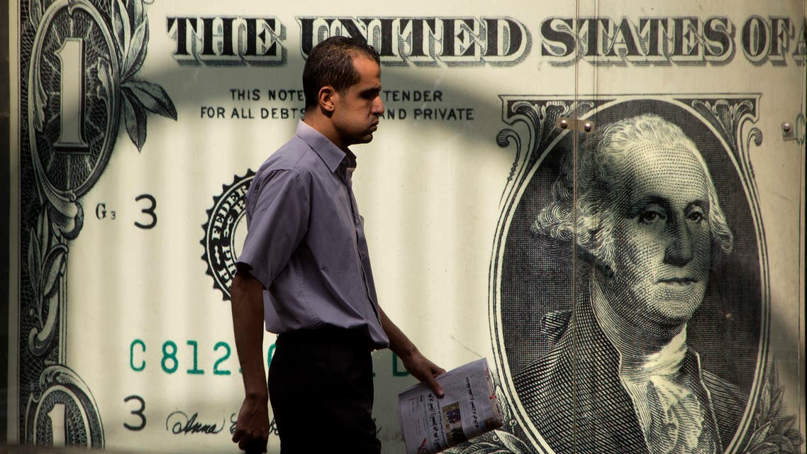 An Egyptian man walks past a poster showing a U.S. dollar outside an exchange office in Cairo, Egypt, Thursday, Nov. 3, 2016. (Reuters)