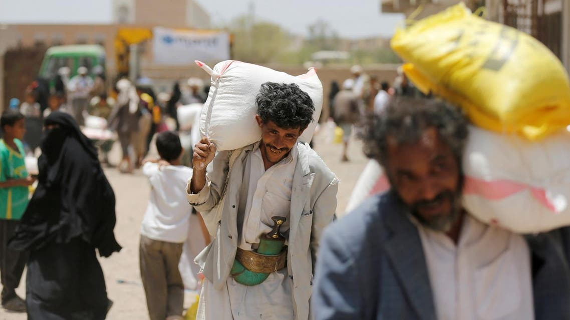 People carry food aid they received from a local charity in Sanaa, Yemen, June 5, 2016. To match Insight YEMEN-SECURITY/CENBANK REUTERS/Khaled Abdullah