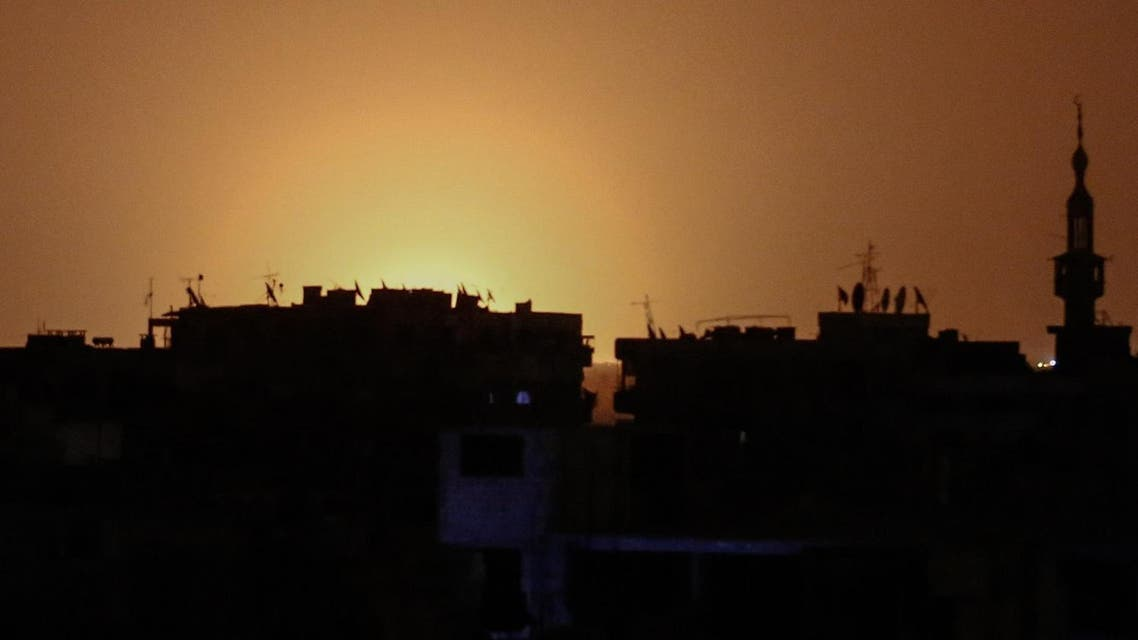 A photo taken from the rebel-held town of Douma shows flames rising in the distance which are believed to be coming from Damascus International Airport following an explosion early in the morning of April 27, 2017. (AFP)