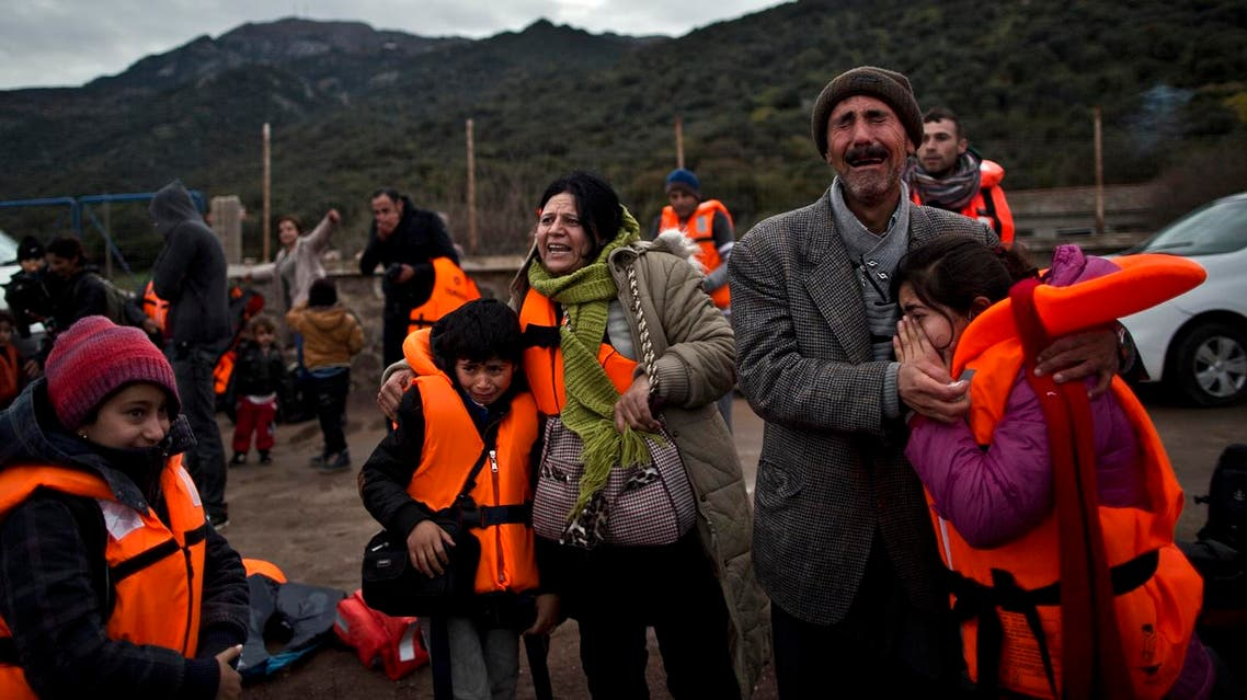 In this Thursday, Dec. 3, 2015 photo, Yazidi refugee Samir Qasu, 45, right, from Sinjar, Iraq, and his wife Bessi, 42, cry while embracing their children, Dunia, 13, and Dildar, 10, shortly after arriving on a vessel from the Turkish coast to the northeastern Greek island of Lesbos. (AP)