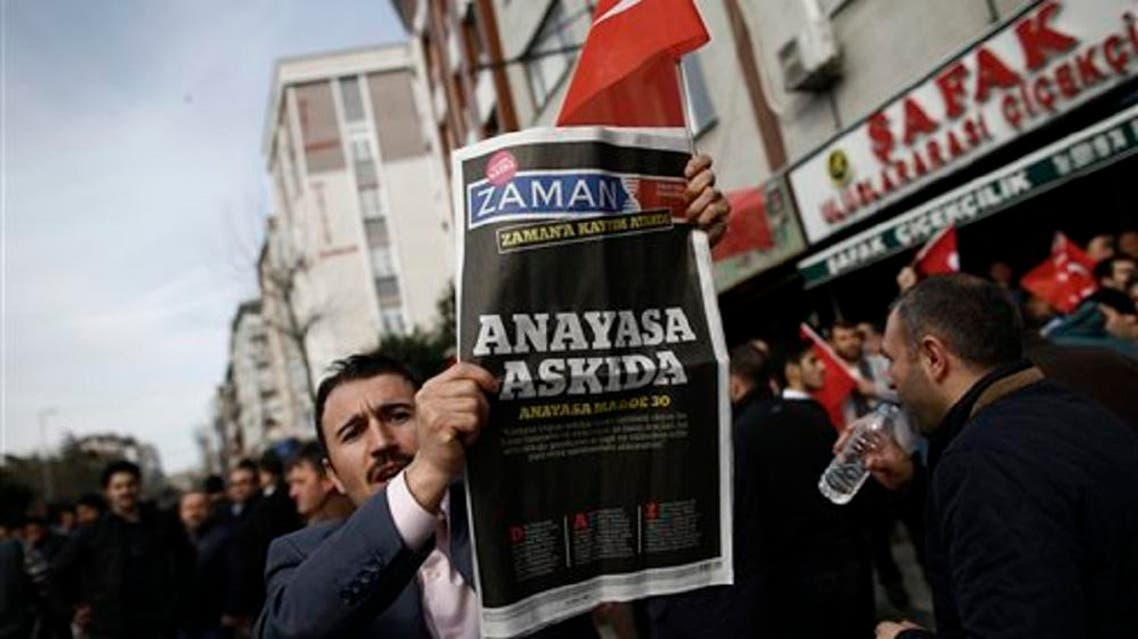 A man holds the copy of  Zaman newspaper  outside the headquarters of Zaman newspaper in Istanbul, on March 6, 2016. (AP)