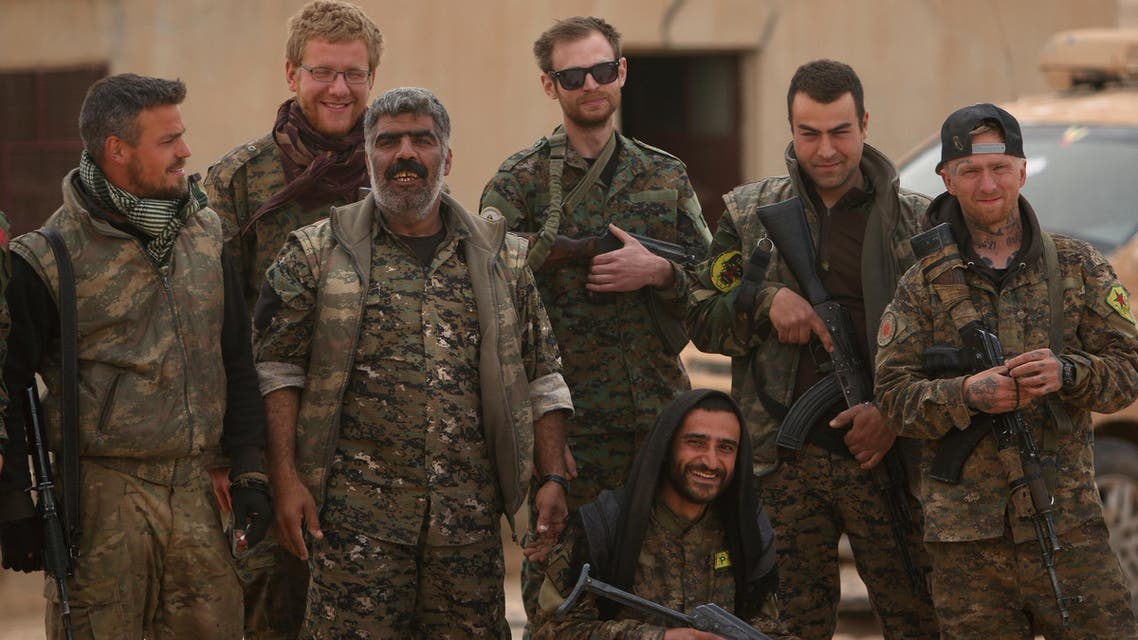 Syrian Democratic Forces (SDF) fighters pose with foreign volunteer fighters inside Tabqa military airport after taking control of it from Islamic State fighters, west of Raqqa city, Syria April 9, 2017