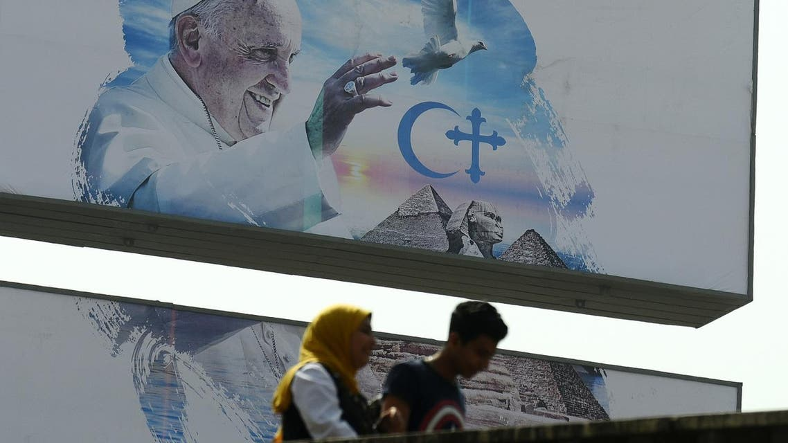 Egyptians walk past a welcome banner bearing a portrait of Pope Francis a day ahead of his visit to the capital Cairo, on April 27, 2017. (AFP)