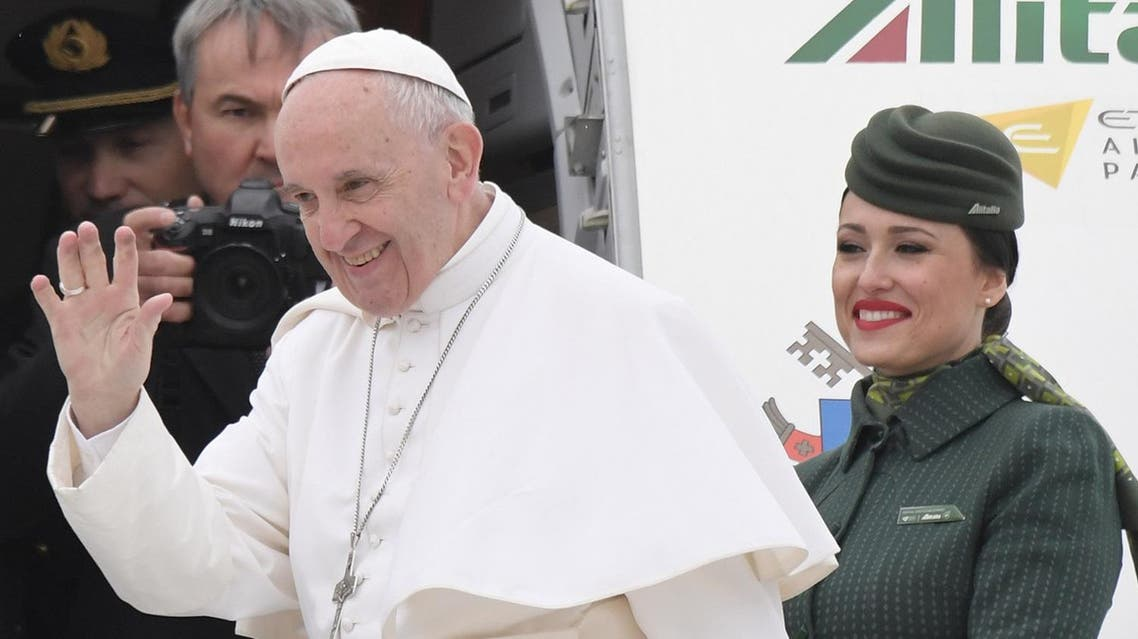 Pope Francis waves to the press as he is welcomed by Alitalia's personnel prior his flight to Egypt, on April 28, 2017 at Rome's Fiumicino airport. Pope Francis heads for a two-day visit in Egypt for talks with the grand imam of the capital's famed Al-Azhar mosque in Cairo, but also to show solidarity with Coptic Christians targeted by violence in Egypt. (AFP)