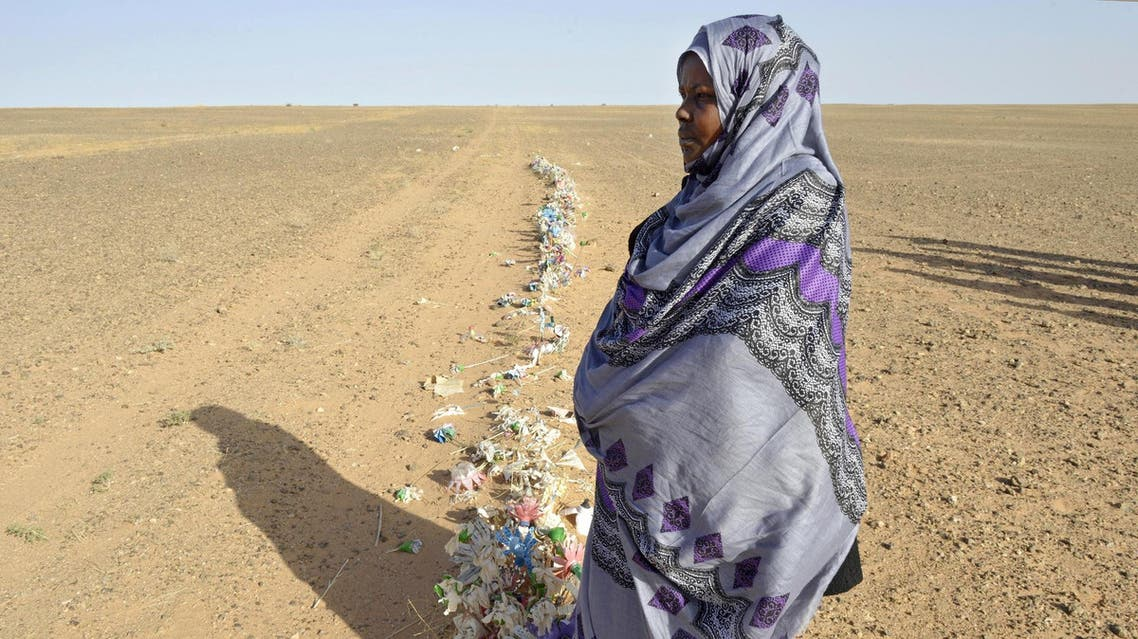 Zghala, a Saharawi woman, stands in front of fake flowers looking at Moroccan soldiers in the Al-Mahbes area as she accompanies her 14-year-old son to show him the wall separating the Polisario controlled Western Sahara from Morocco on February 3, 2017. (File Photo: AFP)