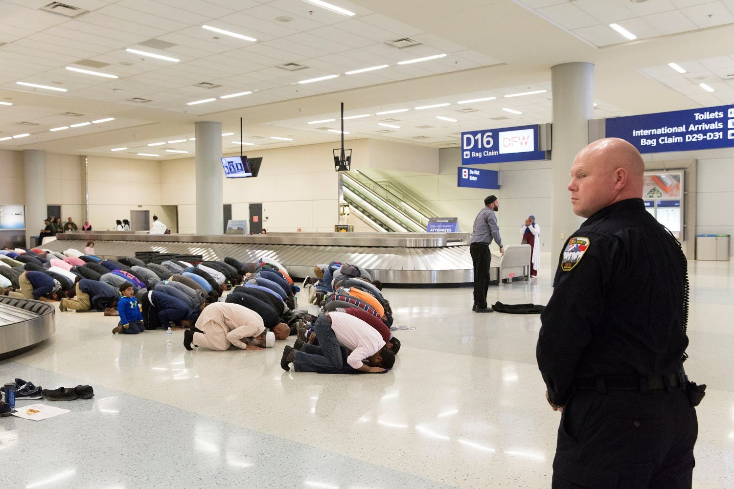 People gather to pray in baggage claim during a protest against the travel ban imposed by US President Donald Trump's executive order, at Dallas/Fort Worth International Airport in Dallas, Texas, US January 29, 2017 (Photo: Reuters/Laura Buckman)