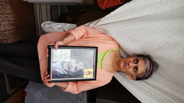 Christina's mother holds on to her daughters photo. (Alarabiya)