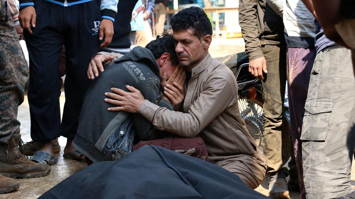 A Syrian man cries on the shoulder of a comrade next to a body at the site of a reported car bomb explosion in the rebel-held town of Azaz in northern Syria on May 3, 2017. Five people killed were reportedly killed, four civilians and one police officer. (AFP)