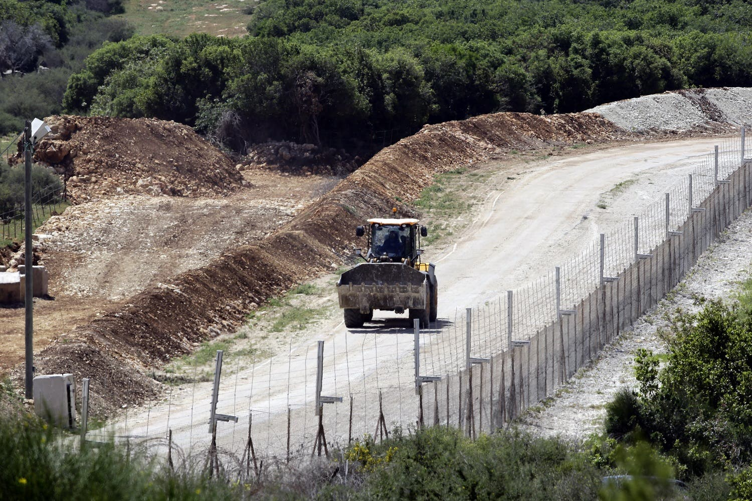 A general view taken from the Lebanese side of the border with Israel shows an Israeli bulldozer driving as they erect new fortifications near the Israeli kibbutz of Hanita on April 20, 2017. (AFP)
