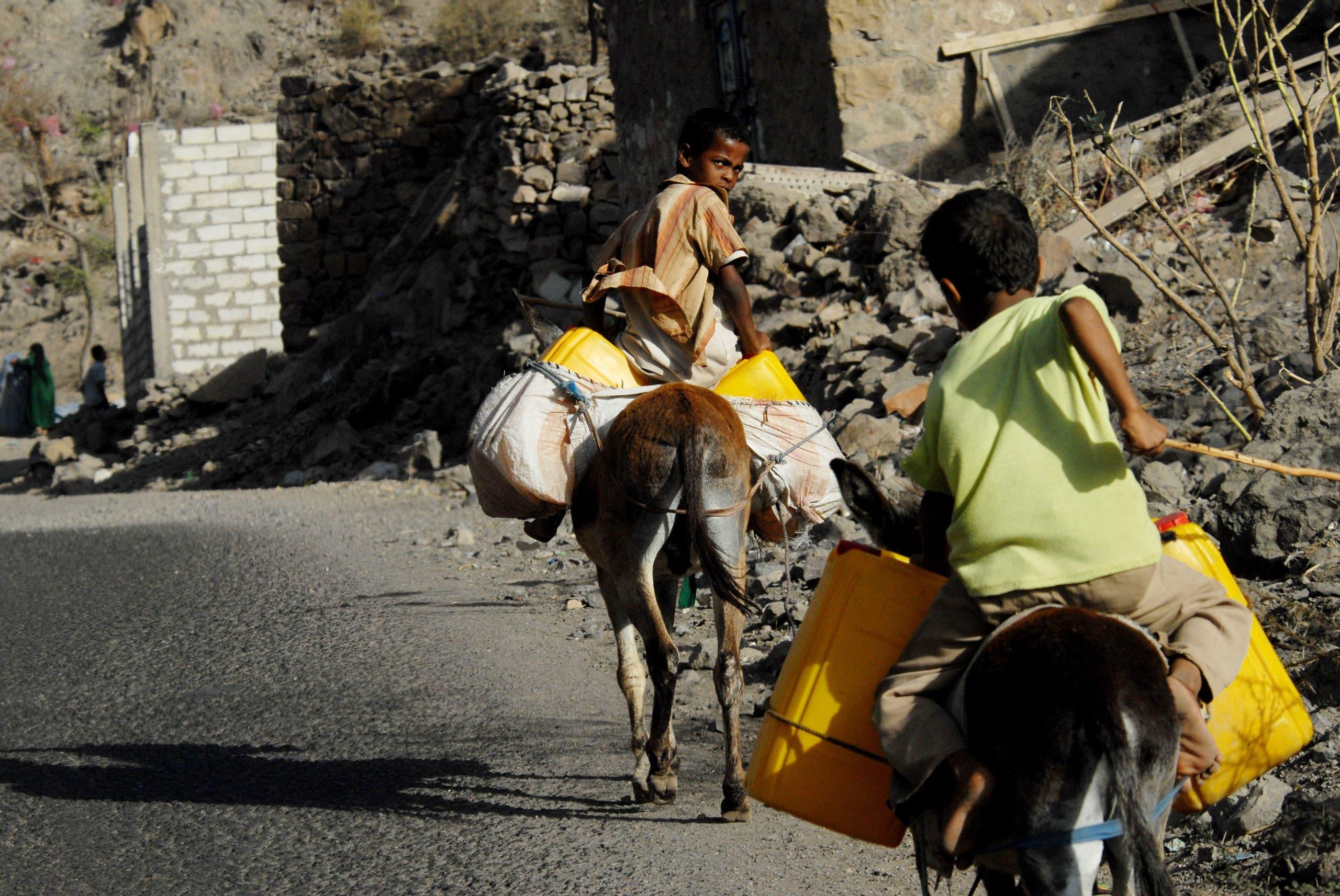أطفال يمنيون ينقلون المياه التي جمعوها في بئر (أرشيفية)