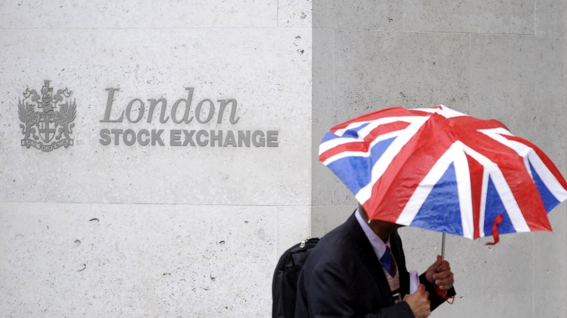 A worker shelters from the rain under a Union Flag umbrella as he passes the London Stock Exchange in London, Britain, October 1, 2008. reuters