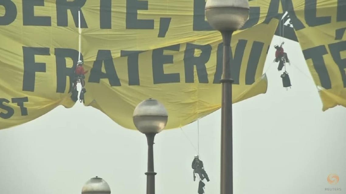 """Greenpeace climbers unfurled a banner with the French republican slogan """"Liberty, Equality, Fraternity"""" and the word """"Resist"""" on the Eiffel Tower on Friday May 5. (Screengrab: Reuters)"""