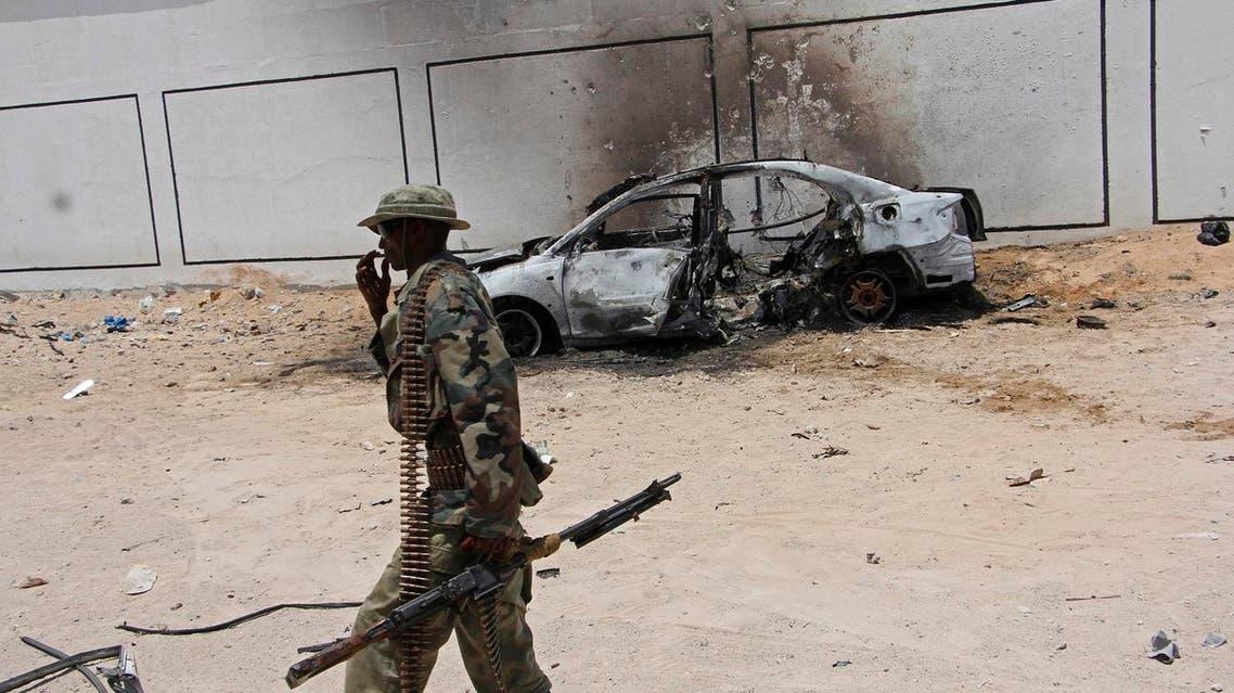 A Somali soldier walks near the wreckage of a car bomb blast near Aden Abdule international airport in Mogadishu on April, 16, 2017. (AP)