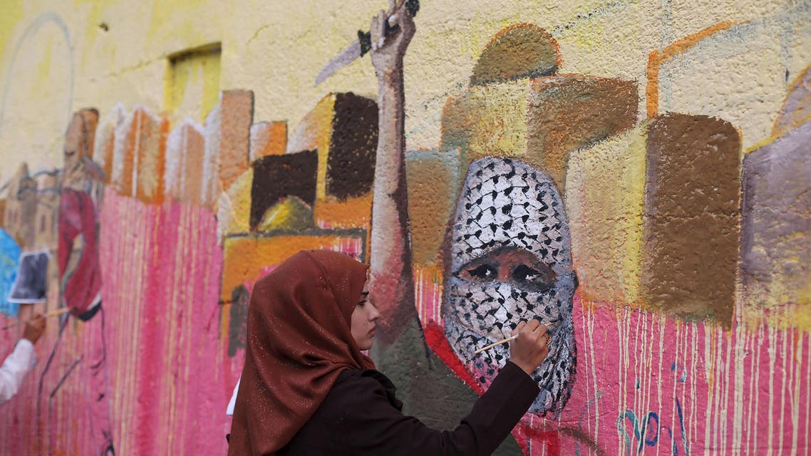 A Palestinian woman paints a mural, depicting a masked Palestinian holding a knife, in support of Palestinians committing stabbing attacks against Israelis, in Rafah in the southern Gaza Strip November 3, 2015. (Reuters)