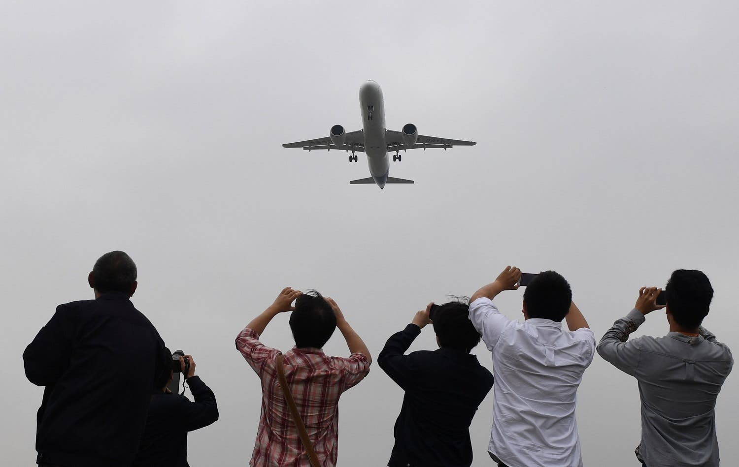 Spectators take photos as they watch the Comac C919, China's first large passenger jet, coming in for a landing on its maiden flight at Shanghai's Pudong airport. (Reuters)