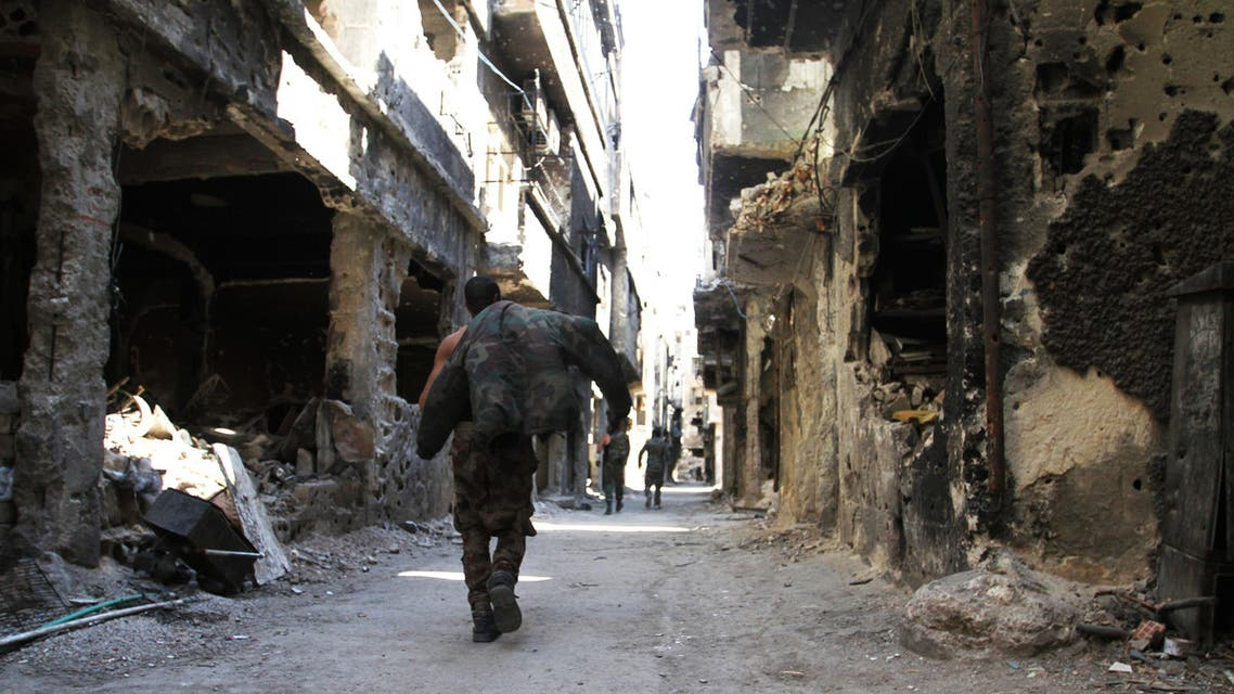 Men walk past destroyed buildings in the Yarmuk Palestinian refugee camp in the Syrian capital Damascus on April 6, 2015. Around 2,000 people have been evacuated from the camp after the Islamic State group seized large parts of it. At least 26 people, including civilians as well as fighters from IS and Palestinian factions, had been killed in the camp according to the Syrian Observatory for Human Rights. A
