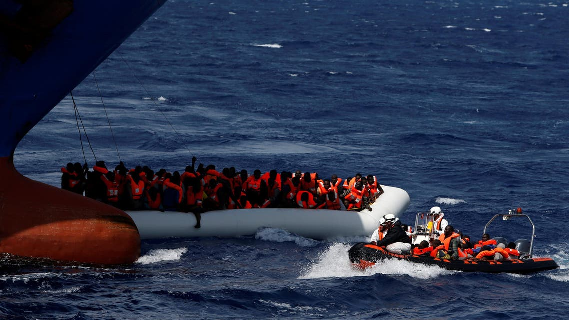 Migrants in a rubber dinghy hang on to ropes beneath the bow of the Panama-registered ship Tuna 1, as a rigid hull inflated boat (RHIB) of the Malta-based NGO Migrant Offshore Aid Station (MOAS) transfers migrants to the ship, after some migrants on another rubber dinghy drowned in the central Mediterranean in international waters off the coast of Libya, April 16, 2017