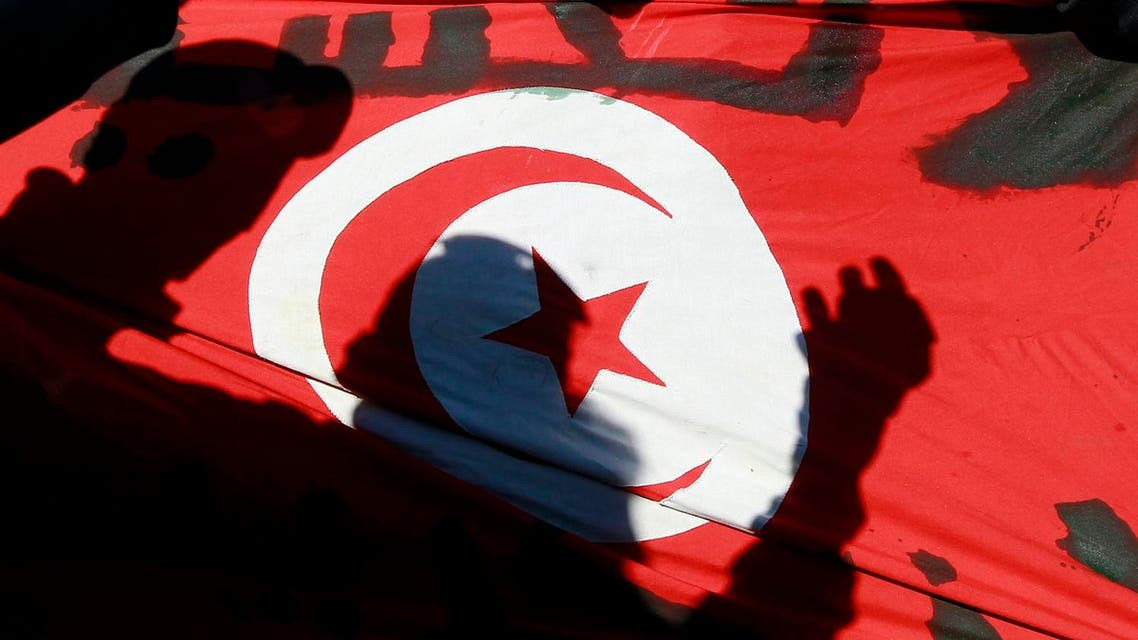 Shadows of people are seen on the Tunisian flag. (File photo: Reuters)
