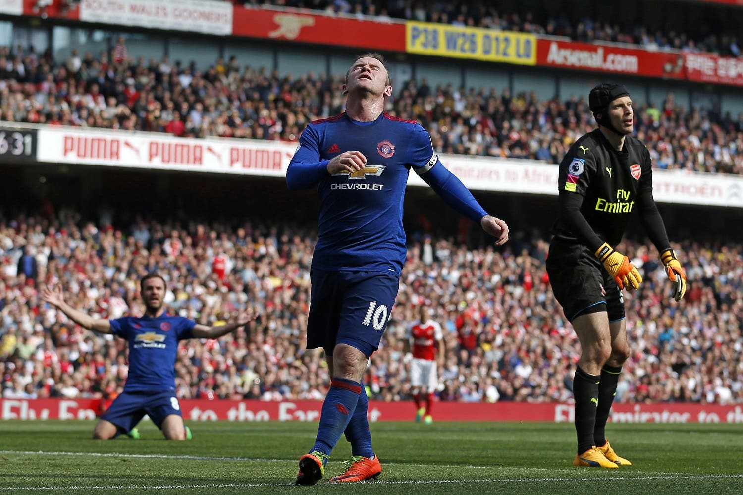 Manchester United's English striker Wayne Rooney (C) reacts after having a shot saved by Arsenal's Czech goalkeeper Petr Cech (R) during the English Premier League football match between Arsenal and Manchester United at the Emirates Stadium in London on May 7, 2017. (AFP)