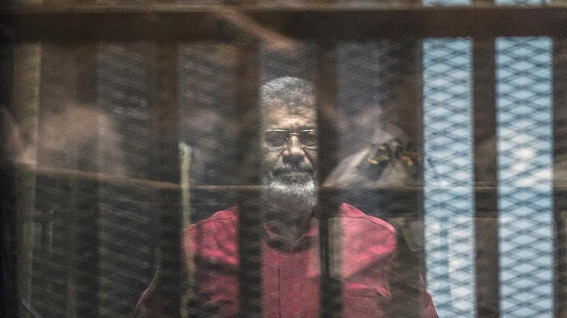 Egypt's ousted Islamist president Mohamed Morsi, wearing a red uniform, stands behind the bars during his trial in Cairo at the police academy in Cairo on April 23, 2016. An Egyptian court postponed its verdict and sentence in the trial of ousted Islamist president Mohamed Morsi, who is charged with spying for Qatar. AFP