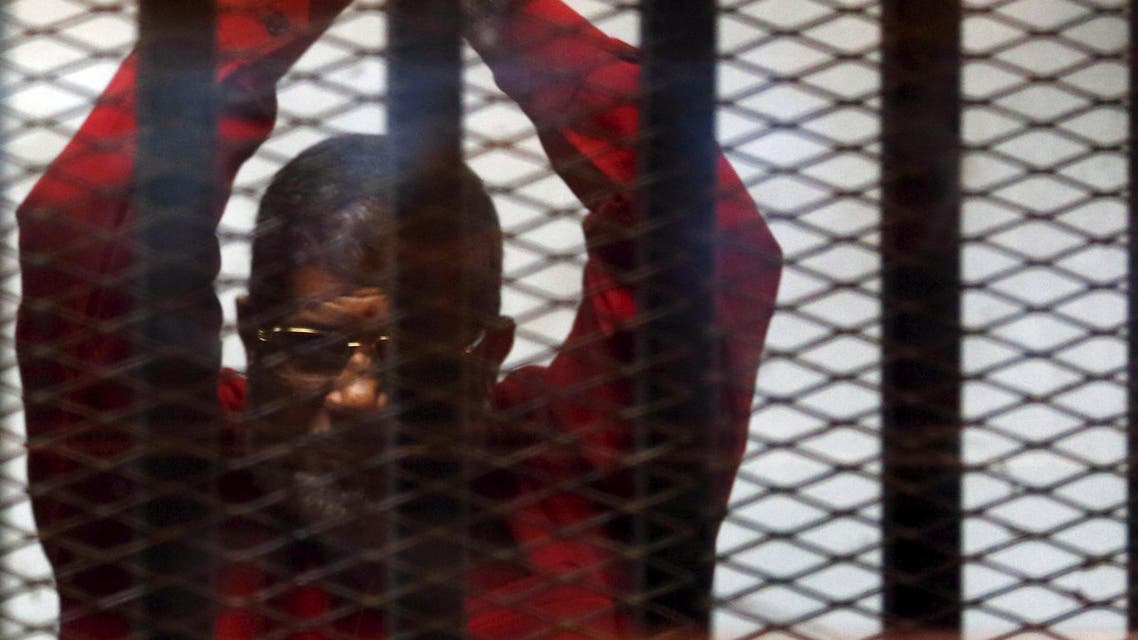 Deposed President Mohamed Mursi greets his lawyers and people from behind bars at a court wearing the red uniform of a prisoner sentenced to death, during his court appearance with Muslim Brotherhood members on the outskirts of Cairo, Egypt, June 21, 2015. (Reuters)