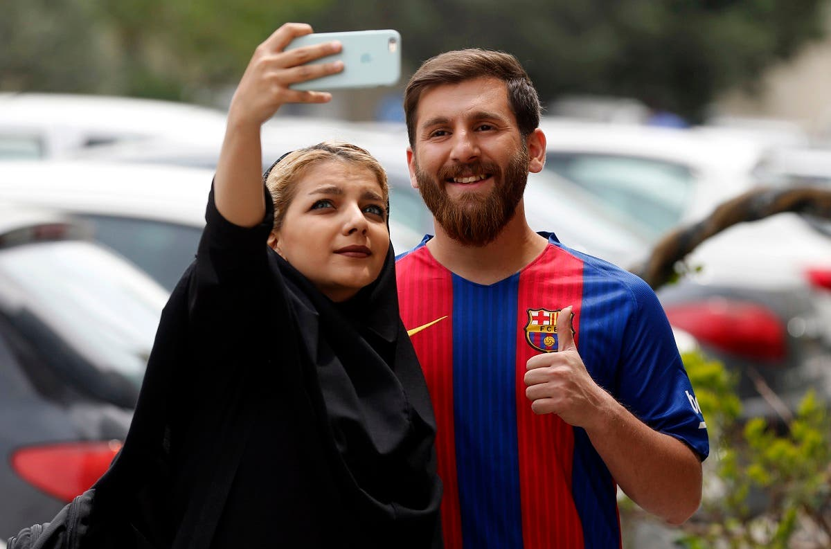 Reza Parastesh, a doppelganger of Barcelona and Argentina's footballer Lionel Messi, poses for a picture with fans in a street in Tehran on May 8, 2017. (AFP)