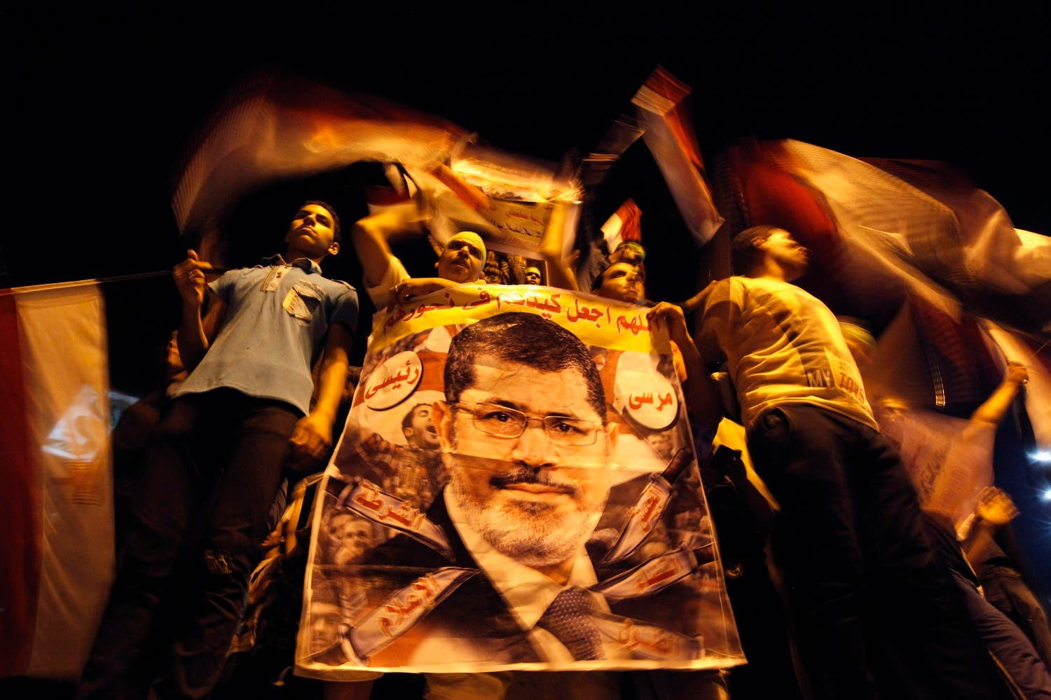 Members of the Muslim Brotherhood and supporters of deposed Egyptian President Mohamed Mursi hold a banner with his picture, in Cairo July 12, 2013. (Reuters)