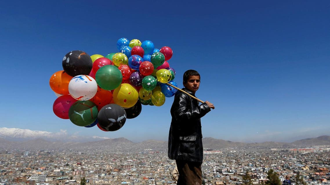 An Afghan boy holds balloons for sale on a hilltop during Afghan spring and new year celebrations in Kabul on March 23, 2017. (Reuters)