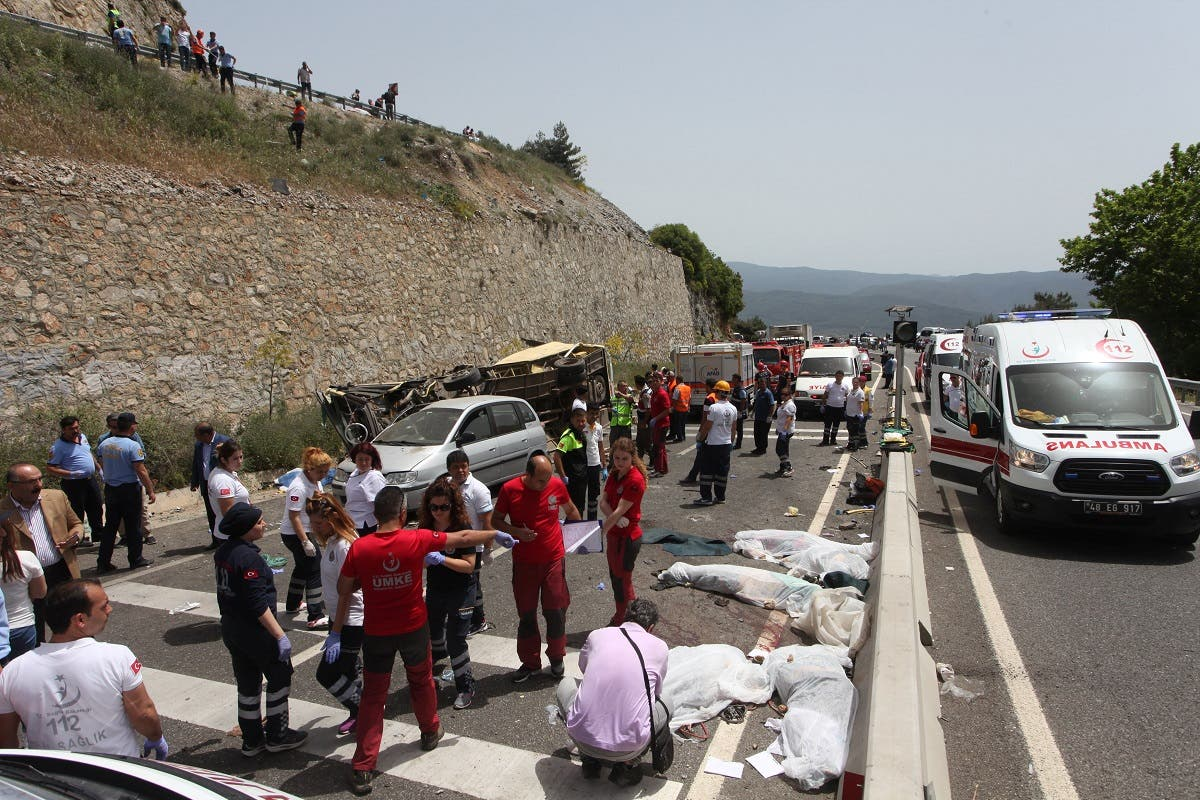 Medics and rescue workers stand at the scene after a tourist bus crashed near the southwestern holiday town of Marmaris. (Reuters)