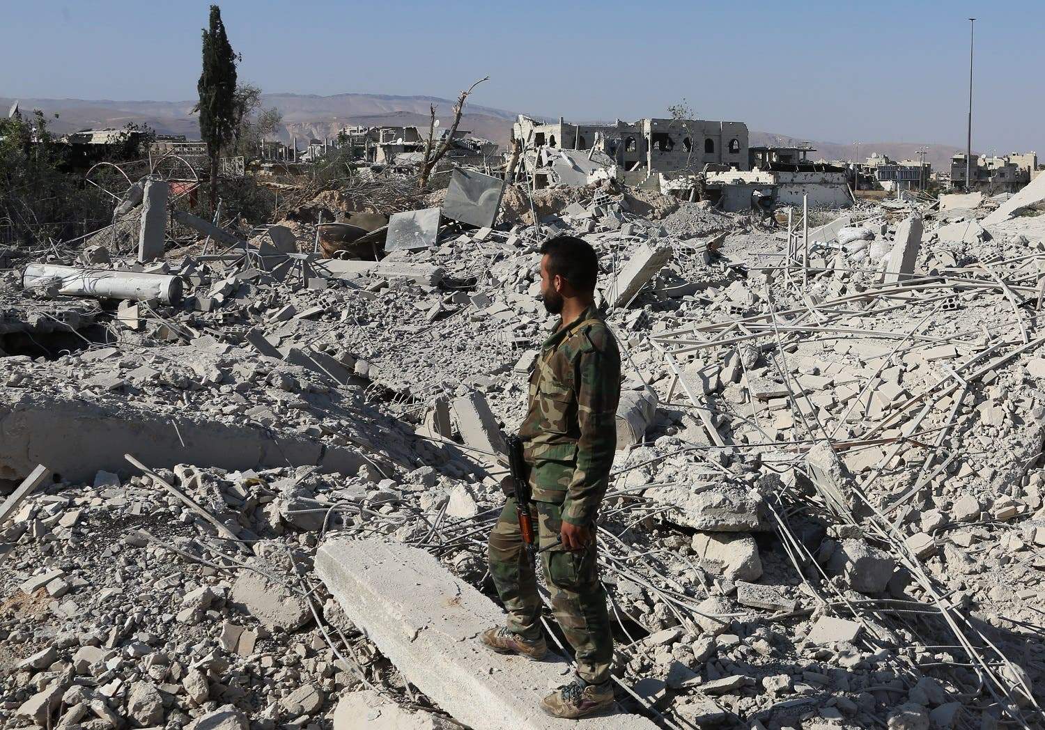 A member of the Syrian pro-government forces stands on the rubble of destroyed buildings as troops advance through Qabun district, on the outskirts of the capital Damascus, on May 13, 2017, during an offensive to retake the area from opposition fighters. (AFP)