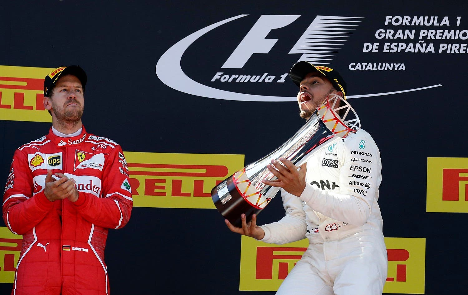 Mercedes driver Lewis Hamilton  (right), and Ferrari's  Sebastian Vettel of Germany celebrate after placing first and second at the Spanish Formula One GP. (AP)