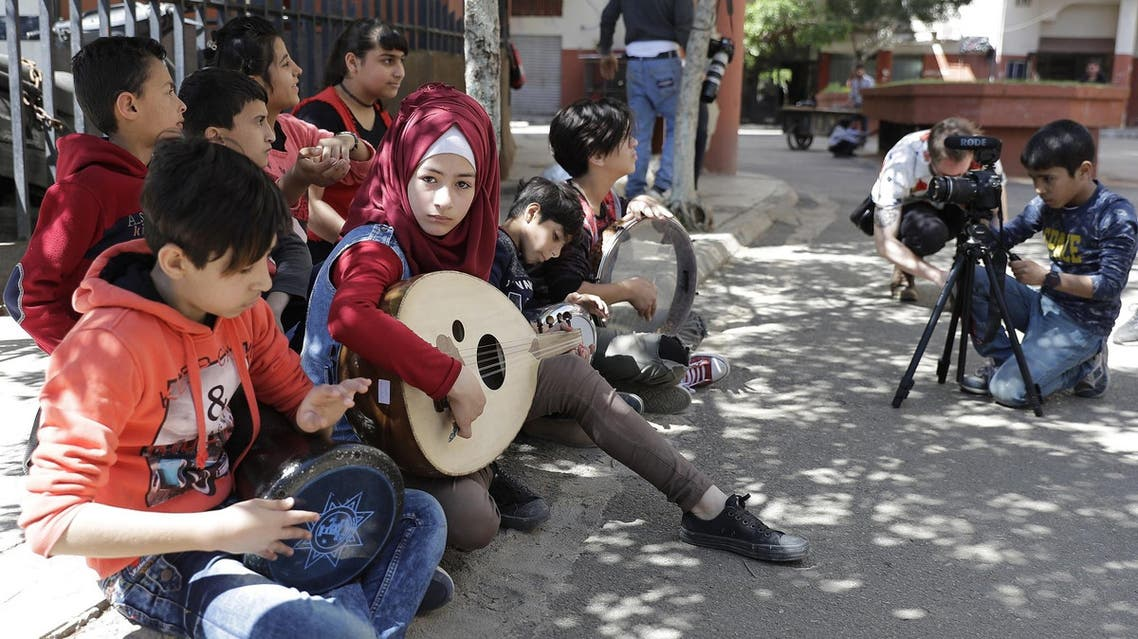 Syrian refugees from Minbej, nine-year-old Mostafa Abdallah (R) and thirteen year old Hanadi al-Hajj Abdallah (C) film a scene in Beirut as part of a refugee programme, the Refugee Film Project. (AFP)