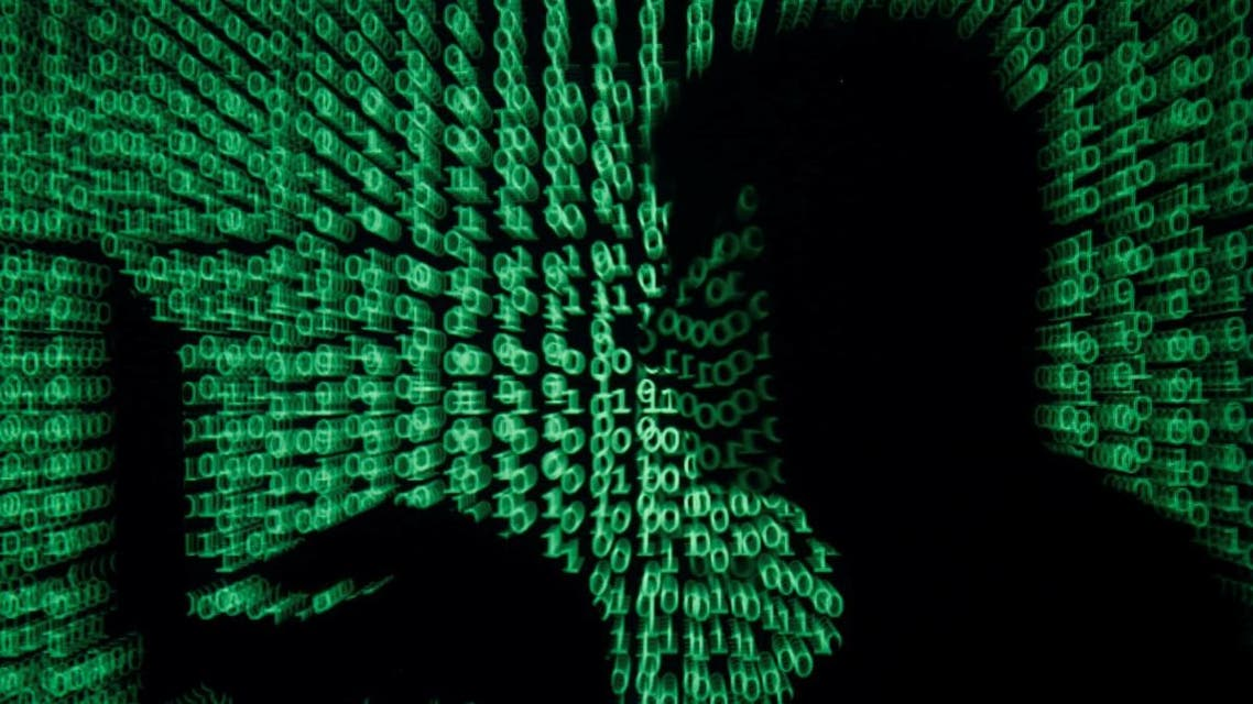 Man holds laptop computer as cyber code is projected on him in this illustration picture. (Reuters)