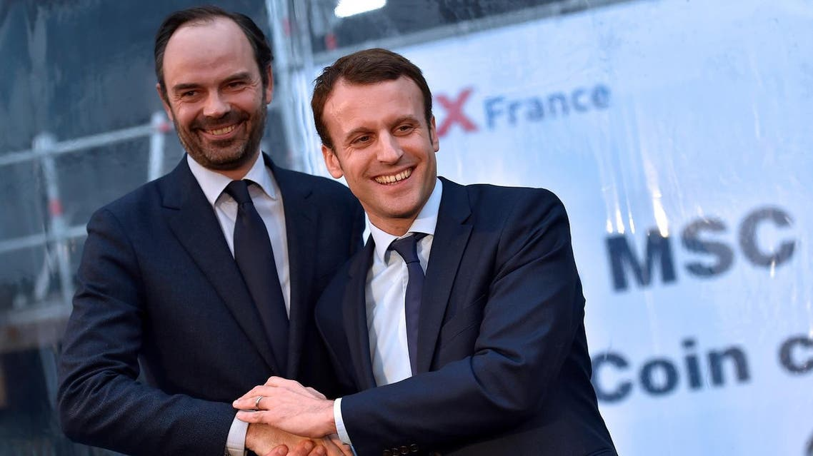 (FILES) This file photo taken on February 1, 2016 shows French Economy Minister Emmanuel Macron (R) shaking hands with mayor of Le Havres Edouard Philippe during the MSC Meraviglia cruise ship coins ceremony at the STX shipyards in Saint-Nazaire, western France. Edouard Philippe was appointed French Prime Minister on May 15, 2017. A(P)
