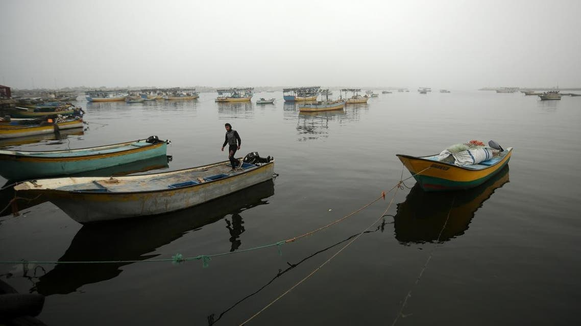A Palestinian fisherman stands on his boat in Gaza City's seaport during heavy fog on February 26, 2017. (AFP)