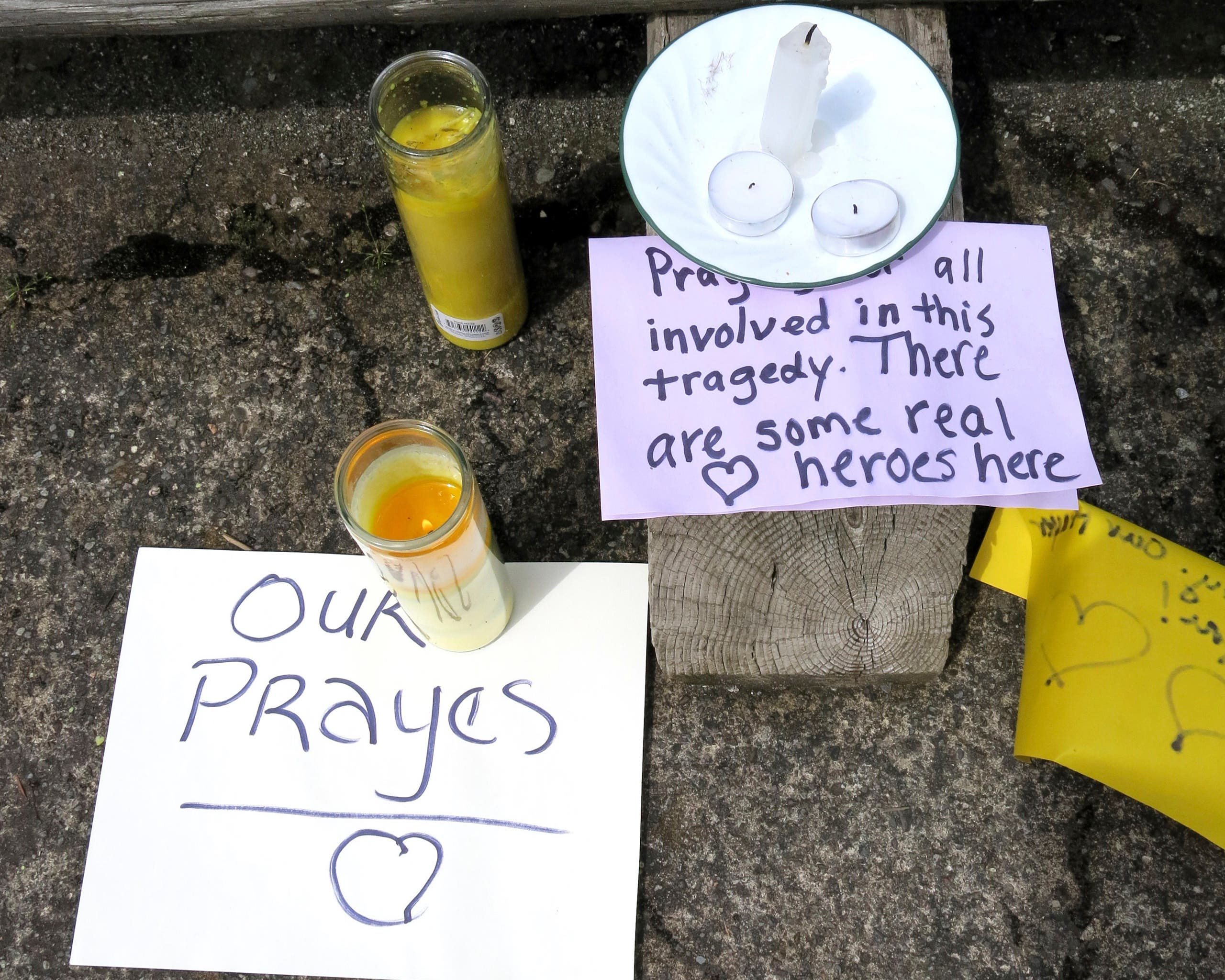 Well-wishing messages and candles for an injured employee are shown outside a grocery store in Estacada, May 15, 2017. (AP)