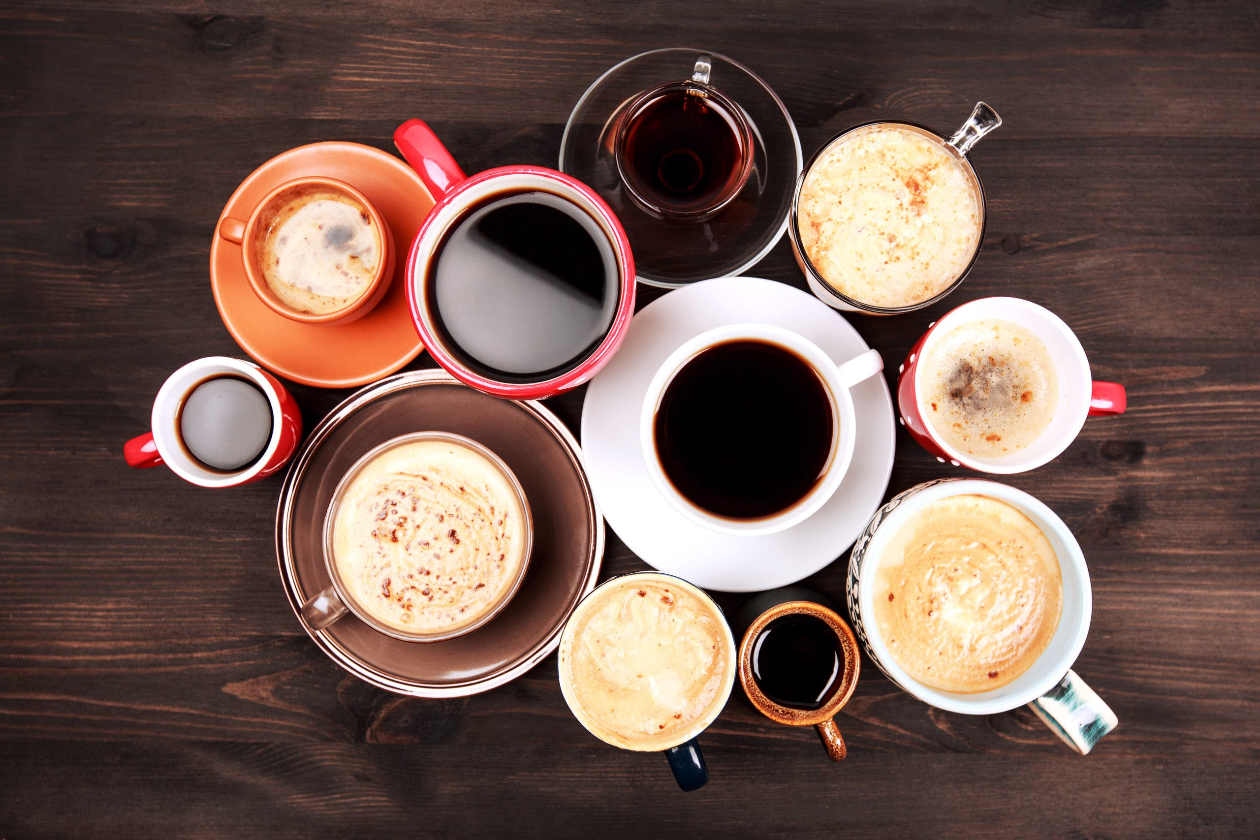 Many cups of coffee are placed on a wooden table. (Stock image)