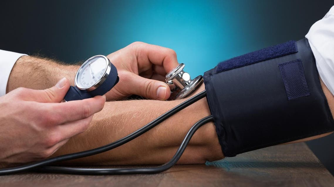 Cropped image of male doctor checking blood pressure of patient at table. (Shutterstock)