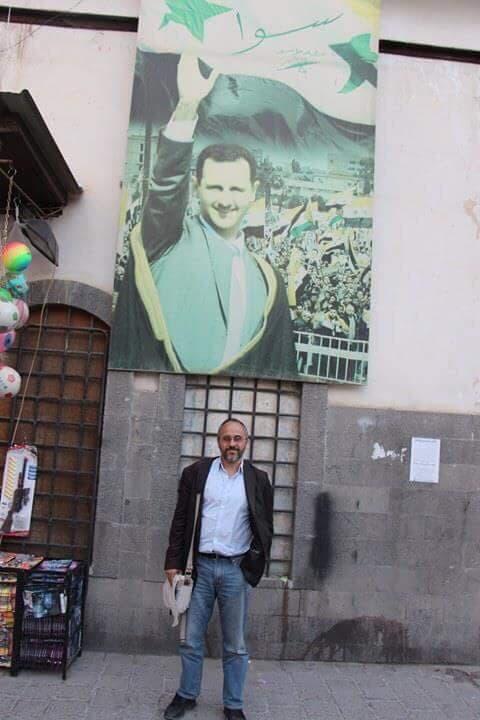 الصحافي بجانب صورة للأسد في سوق الحميدية