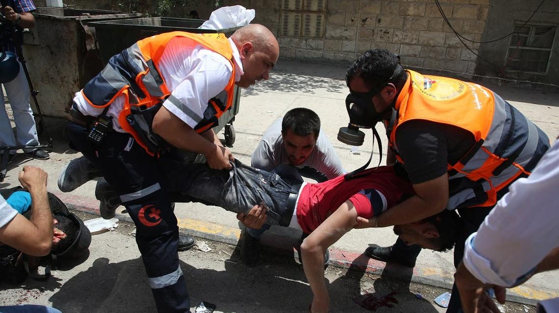 Palestinian medics carry the body of a man who according to Palestinian officials was killed by Israeli settlers during clashes near the Hawara military checkpoint. (AFP)