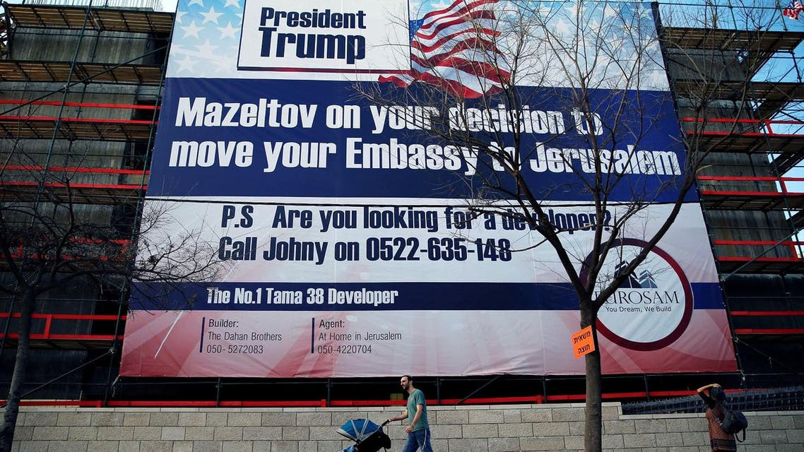 People walk past a giant banner on a building congratulating US President-elect Donald Trump, in Jerusalem, January 20, 2017. (Reuters)