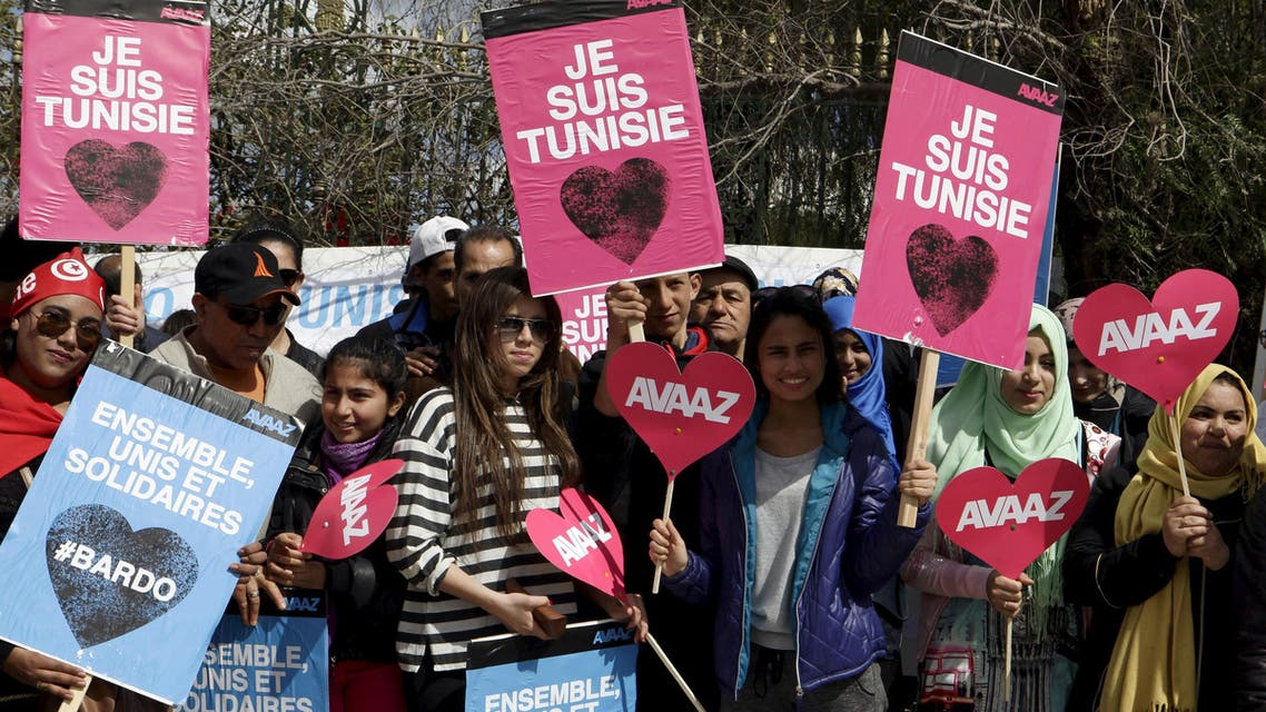"""Tunisians hold posters that read """"I am Tunisia"""" during a march against extremism outside the Bardo Museum in Tunis March 29, 2015. reuters"""