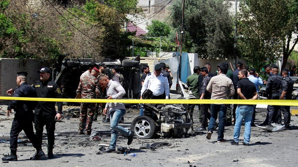 Iraqi security forces inspect the site of a car bomb attack in Baghdad, on May 14, 2017.